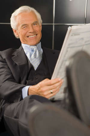 financial newspaper: Portrait of a businessman holding a financial newspaper in an office and smiling LANG_EVOIMAGES