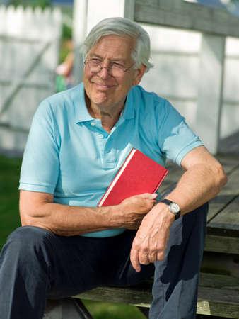 man holding book: Senior man holding book