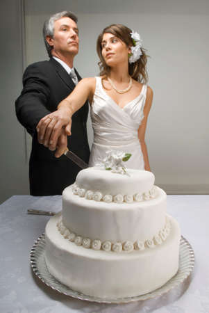 indulging: Serious bride and groom cutting wedding cake LANG_EVOIMAGES