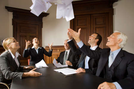 hands lifted up: Businesspeople throwing papers in the air