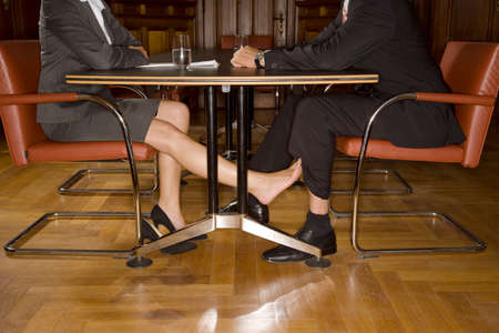 Businesspeople playing footsie under table LANG_EVOIMAGES