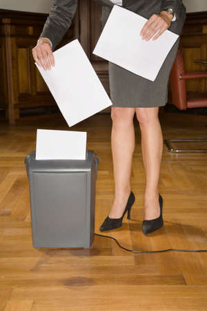 lower section view: Businesswoman shredding papers LANG_EVOIMAGES