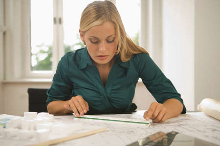 female architect: Young female architect reviewing blueprints