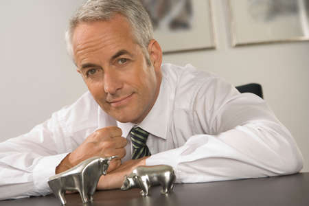 smirking: Portrait of a businessman smirking in front of a bear and a bull figurine LANG_EVOIMAGES