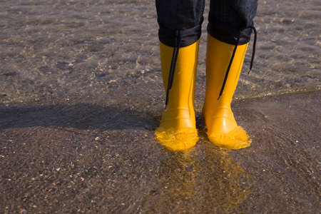 lower section view: Detail of yellow boots standing in water at the beach LANG_EVOIMAGES