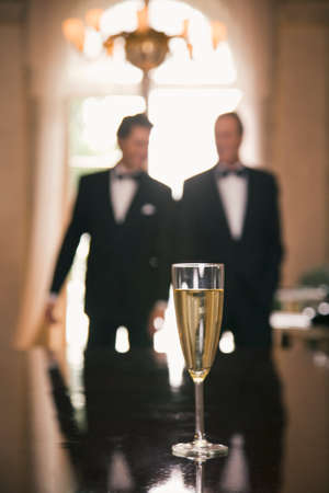 champagne flute: Champagne flute on a table with two men in the background