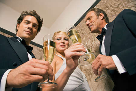 champagne flutes: Portrait of three people holding champagne flutes LANG_EVOIMAGES