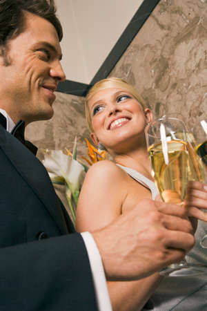 champagne flutes: Close-up of a young couple toasting with champagne flutes