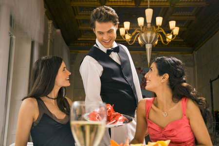 serving: Waiter serving a lobster to two young women
