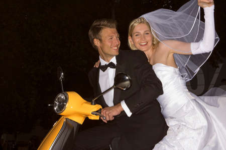 motor scooter: Newlywed couple riding a motor scooter and smiling LANG_EVOIMAGES