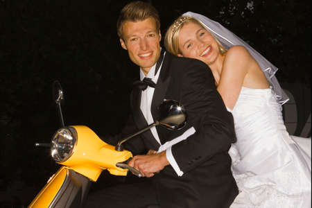 motor scooter: Portrait of a newlywed couple on a motor scooter and smiling