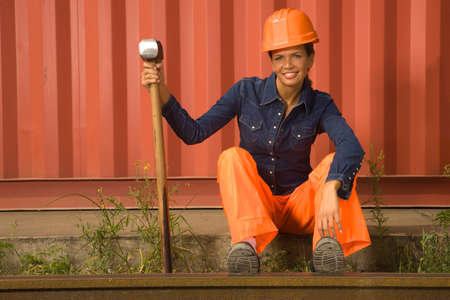 railroad track: Mid adult woman sitting beside a railroad track and holding a hammer LANG_EVOIMAGES