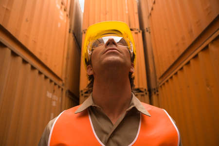 one mid adult man only: Close-up of a male dock worker wearing a hardhat