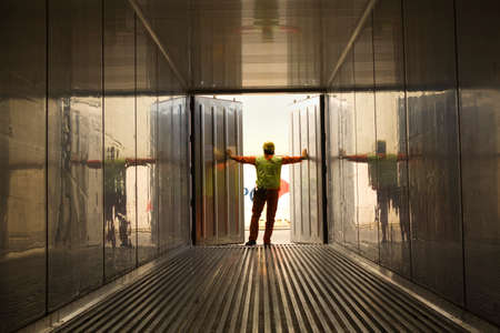 cargo container: Rear view of a male dock worker opening the doors of a cargo container