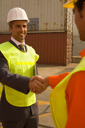 social grace: Businessman shaking hands with a male dock worker