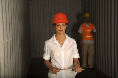rolledup sleeves: Portrait of a female dock worker holding a clipboard and a man standing behind her in a cargo container LANG_EVOIMAGES
