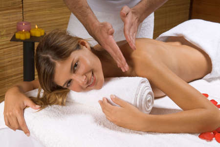 self conscious: Portrait of a young woman receiving a massage from a massage therapist