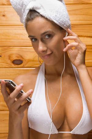 sauna nackt: Portrait einer jungen Frau, die Sauna und das H�ren zu einem MP3-Player