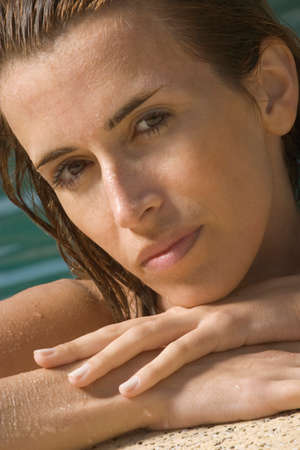 ledge: Portrait of a mid adult woman leaning on the ledge of a swimming pool LANG_EVOIMAGES