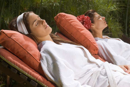 self indulgence: Two young women resting on lounge chairs