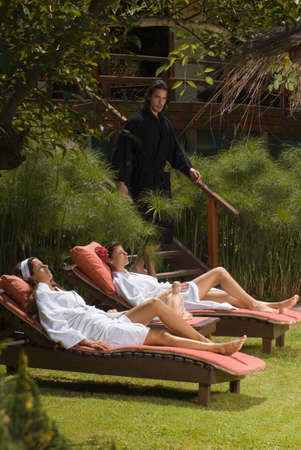 self indulgence: Two young women in bathrobes and resting on lounge chairs