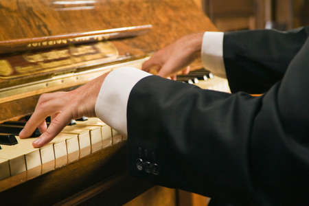 one person only: Close-up of a mans hands playing a piano LANG_EVOIMAGES