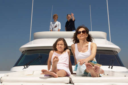 barefoot teens: Young family relaxing on boat LANG_EVOIMAGES