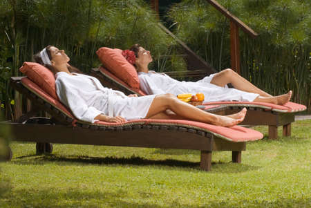 self indulgence: Side profile of two young women in bathrobes and resting on lounge chairs