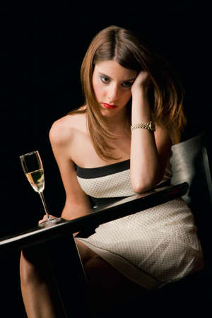 legs crossed on knee: Young woman looking disappointed in a restaurant LANG_EVOIMAGES