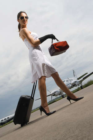 jetset: Side profile of a young woman pulling her luggage