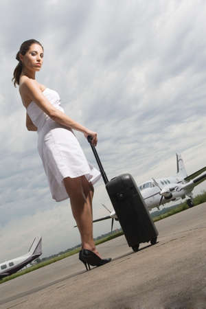 jetset: Side profile of a young woman holding her luggage at an airport