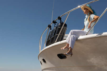 young woman sitting: Young woman sitting on boat LANG_EVOIMAGES