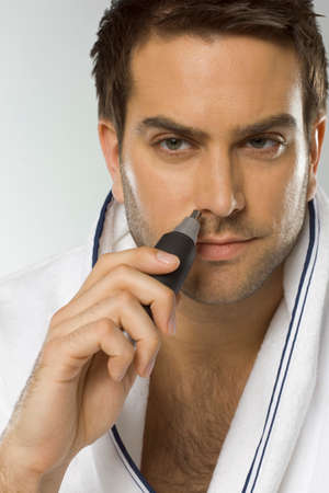 electric trimmer: Mid adult man using nose hair trimmer