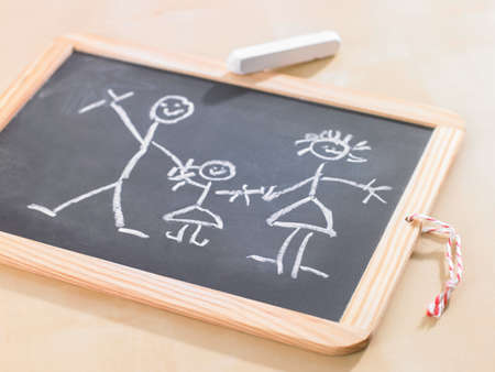 female likeness: Close-up of a childs drawing on a chalkboard depicting a family LANG_EVOIMAGES