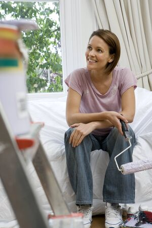 differential focus: Young woman on sofa with paint roller, paint pot on ladder in foreground (differential focus)