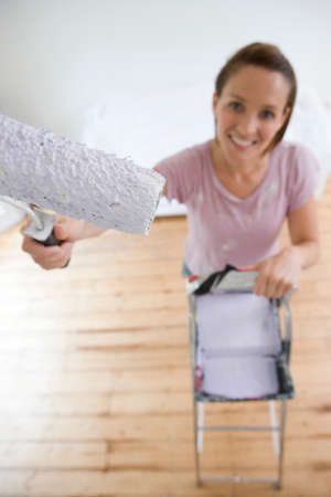 differential focus: Young woman decorating with paint roller, paint tray on ladder, smiling, portrait, elevated view (differential focus)