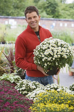 one mid adult man only: Man in red top shopping for flowers in garden centre, holding pot plant, smiling, portrait LANG_EVOIMAGES