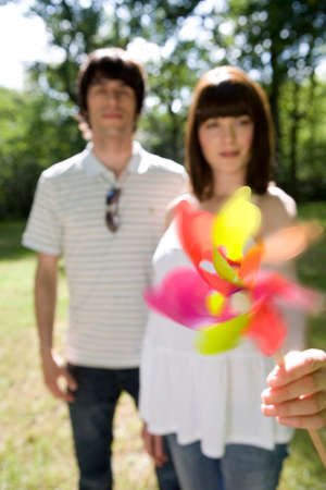 homályos mozgás: Young couple outdoors, woman holding out pinwheel, portrait (blurred motion) LANG_EVOIMAGES