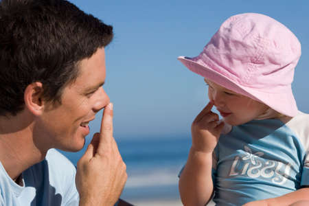 Father playing with daughter (2-3), touching noses with fingers, smiling, close-up, side view Stock Photo