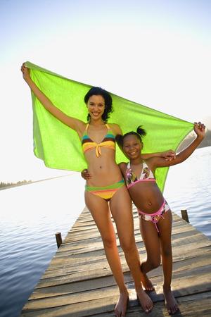 mojar: Madre e hija (7-9) que se coloca en el lago embarcadero, brazos alrededor de la otra, sosteniendo en alto la toalla verde, sonriendo, retrato (inclinaci�n)