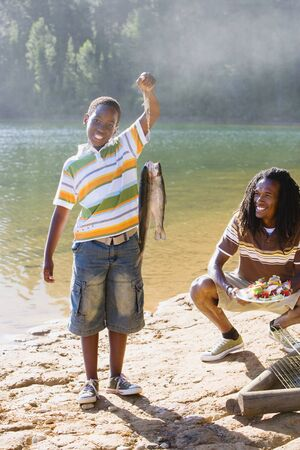 holding aloft: Proud boy (8-10) holding aloft fish on lakeside camping trip, father holding plate of food, smiling, portrait LANG_EVOIMAGES