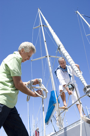 mature men: Two mature men preparing to set sail on yacht, one man untying mooring rope, smiling, low angle view LANG_EVOIMAGES
