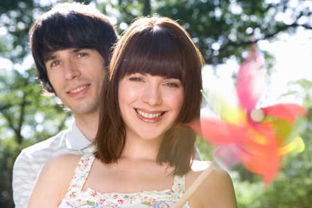 blurred motion: Young couple with pinwheel, smiling, portrait (blurred motion)