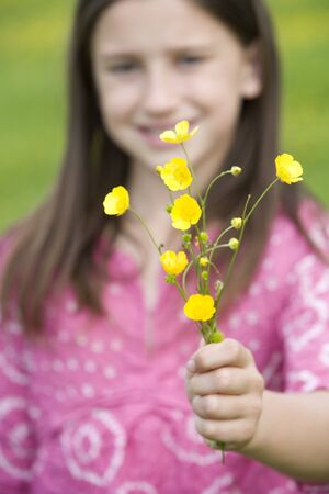 differential focus: Girl (7-9) holding out wild flowers (differential focus)