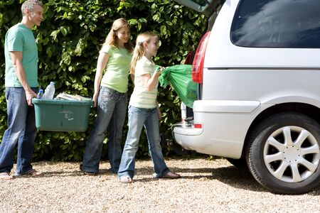 car side view: Family of three loading recycling into car, side view