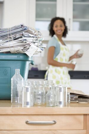 bundling: Glass jars and cans by recycling bin with newspapers in kitchen, woman in background