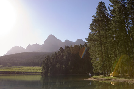 bathed: Solitary man fishing in tranquil lake on camping trip, mountain valley bathed in sunlight (lens flare)