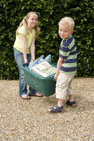 bundling: Brother (4-6) and sister (9-11) lifting recycling bin, smiling, portrait LANG_EVOIMAGES