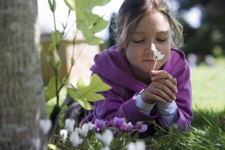 differential focus: Girl (7-9) wearing purple hooded top, lying on grass in garden, smelling flower, eyes closed, close-up, surface level (differential focus)
