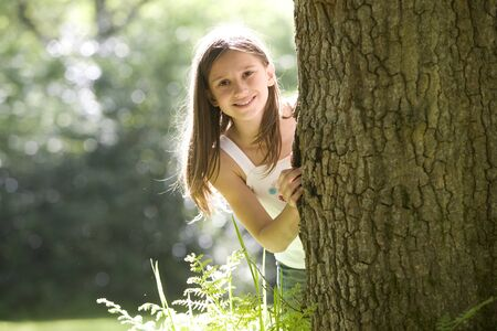 Girl (7-9) peeking out from behind tree, smilng, portrait